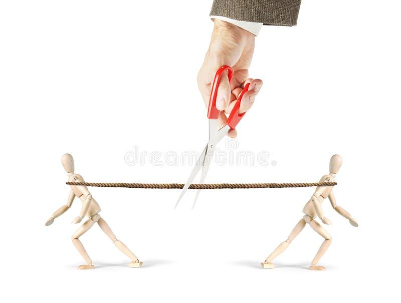 L'homme coupe une corde que deux hommes tirent dans différentes directions photo stock