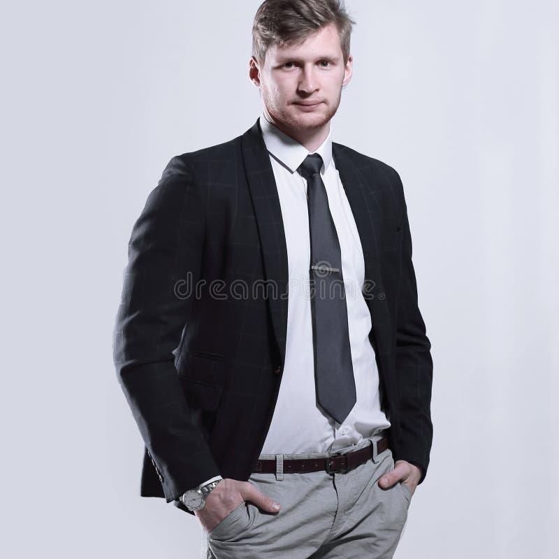 L'homme créatif d'affaires se tient avec ses mains dans des ses poches sur le fond gris images libres de droits