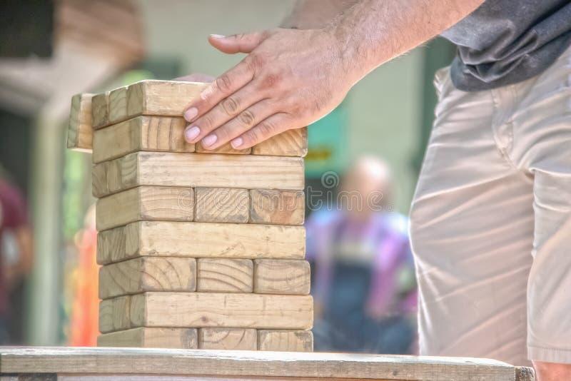L'homme cultivé redresse un bloc en bois de tour de bois de construction empilant le jeu sur une table avec ses mains - personnes photos libres de droits