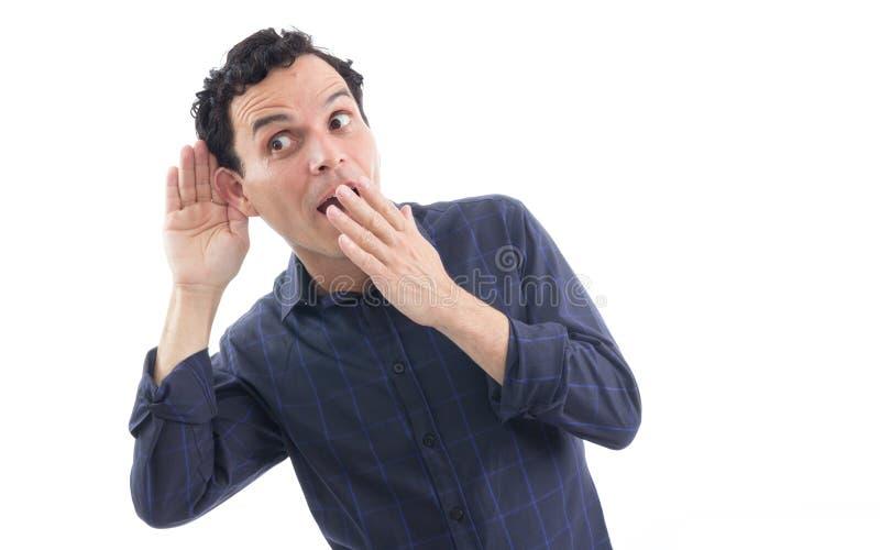 L'homme curieux essaye d'entendre quelque chose La personne porte d photos libres de droits