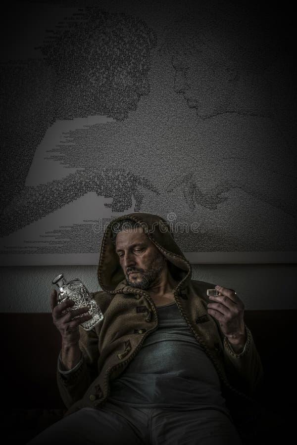 L'homme déçu avec un capot et vident la bouteille en verre gravée d'alcool image libre de droits