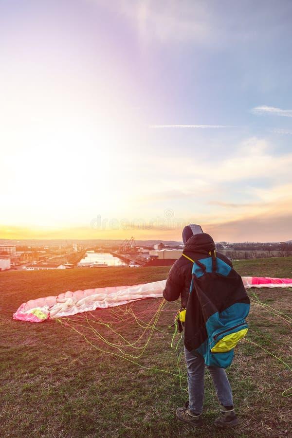 L'homme débarqué plie le parachute se trouvant sur l'herbe verte photographie stock libre de droits