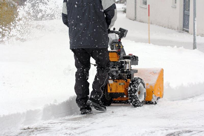 L'homme dégage la neige avec un moulin de neige photo libre de droits