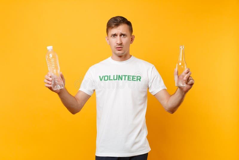 L'homme dégoûté dans le volontaire de T-shirt jugent les bouteilles en verre en plastique d'isolement sur le fond jaune Aide libr photographie stock