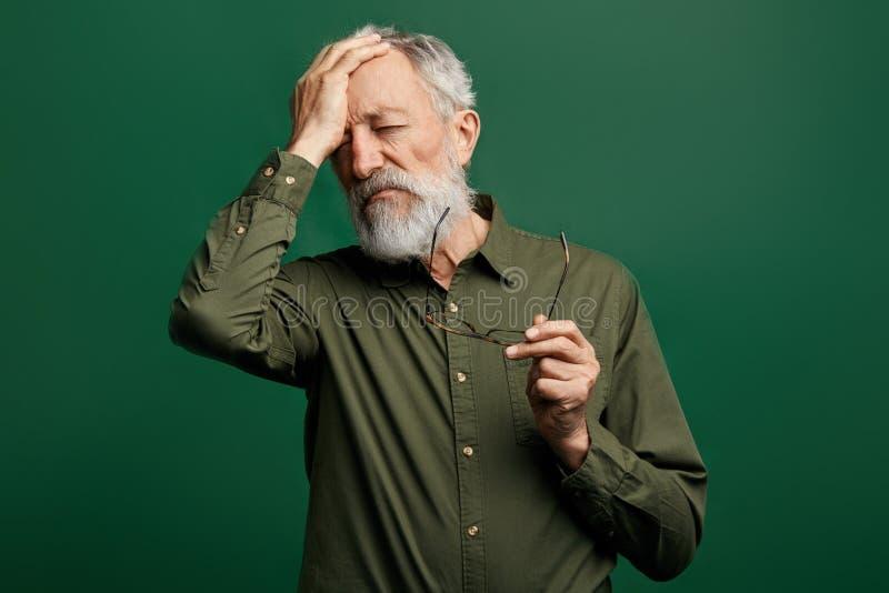 L'homme déprimé triste a un mal de tête, enlevant ses verres et touchant son front photo libre de droits
