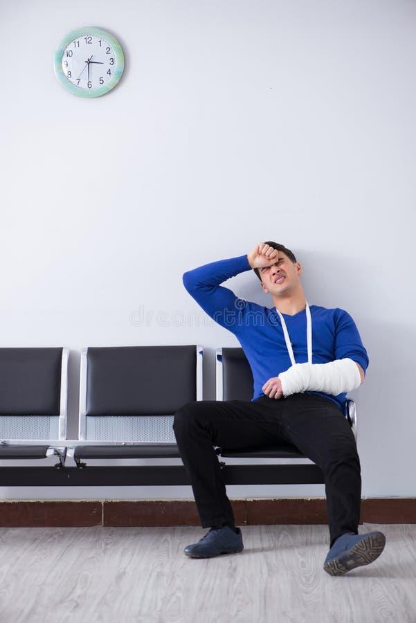 L'homme désespéré attendant son rendez-vous dans l'hôpital avec s'est cassé image stock