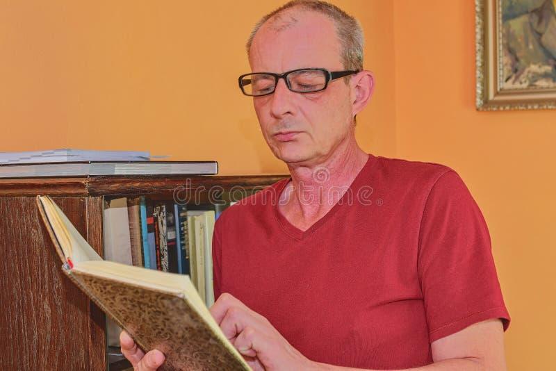 L'homme d'homme âgé par milieu est livre de lecture dans le salon L'homme mûr se tient à côté de la bibliothèque photos libres de droits