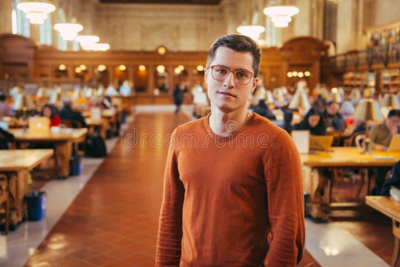 L'homme d'étudiant d'Intelegent en verres se tient dans la salle de lecture de bibliothèque publique photos stock