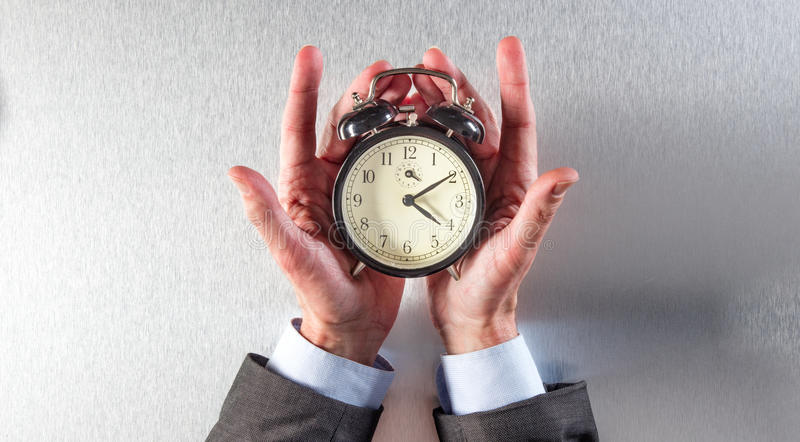 L'homme d'affaires étonné remet tenir un réveil pour la stratégie de temps image libre de droits
