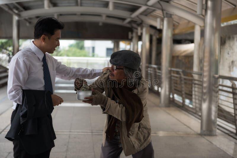 L'homme d'affaires aimable donnent l'argent au sans-abri photo libre de droits