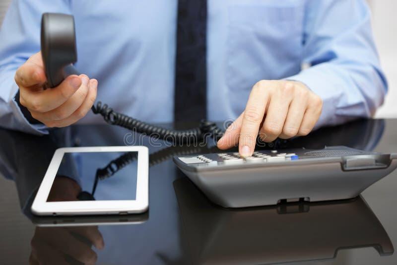 L'homme d'affaires appelle l'appui en lisant le rapport sur COM de comprimé photo stock