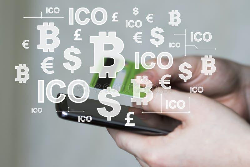 L'homme d'affaires appuie sur le bouton de devises sur la pièce de monnaie d'initiale du téléphone ICO offrant sur le compte élec photographie stock libre de droits
