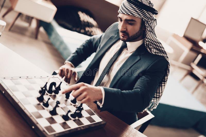 L'homme d'affaires arabe jouant aux échecs et entreprend la démarche photo stock
