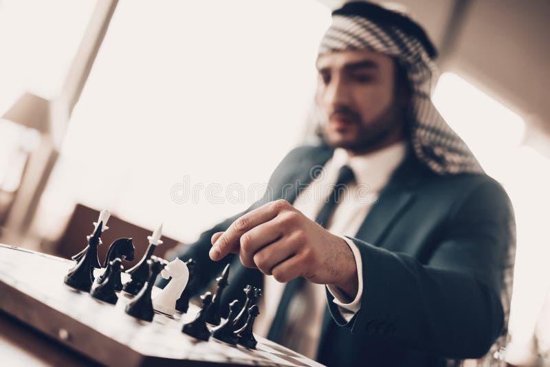 L'homme d'affaires arabe jouant aux échecs et entreprend la démarche photos libres de droits