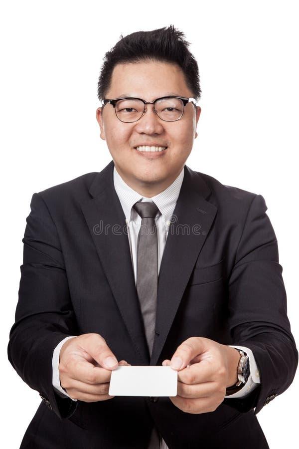 L'homme d'affaires asiatique donnent à une carte blanche avec des les deux la main image stock