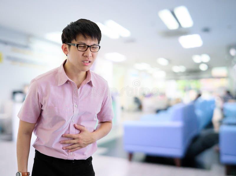 L'homme d'affaires asiatique a la position avec le mal de ventre dans l'hôpital avec la lumière et le fond intérieur photographie stock libre de droits