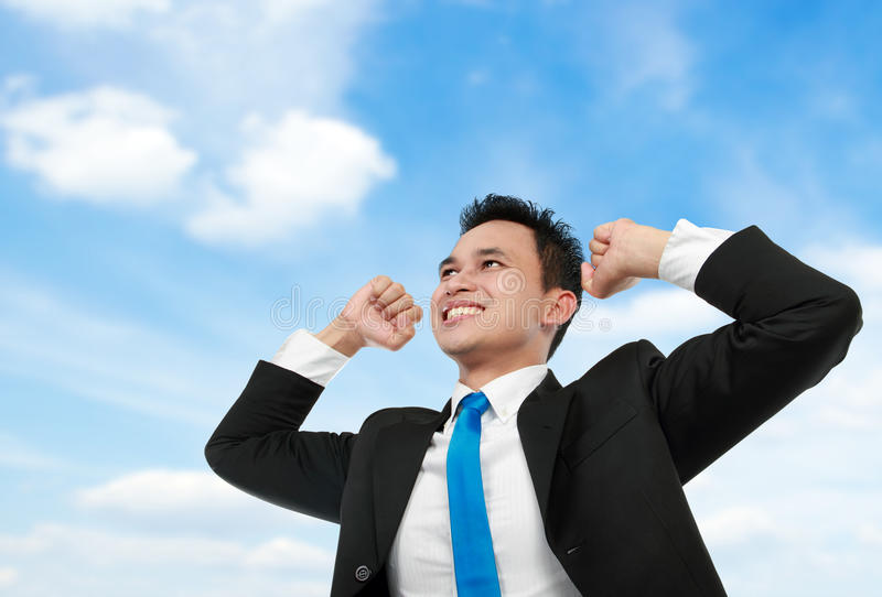L'homme d'affaires avec des bras a augmenté sous le ciel bleu photo stock
