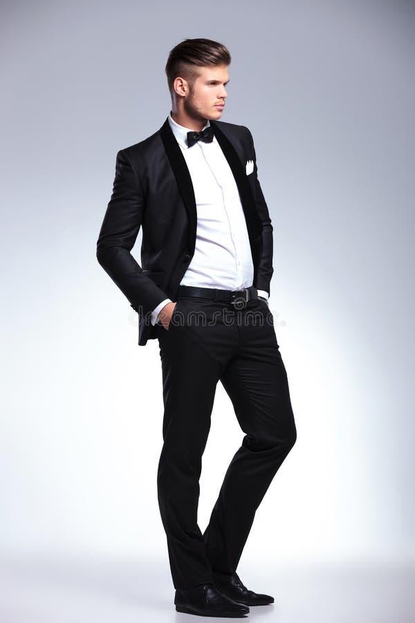 L'homme d'affaires avec des mains dans des poches regarde loin photographie stock