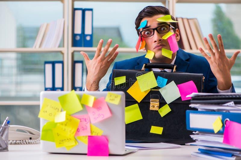 L'homme d'affaires avec des notes de rappel dans le concept multitâche photo libre de droits