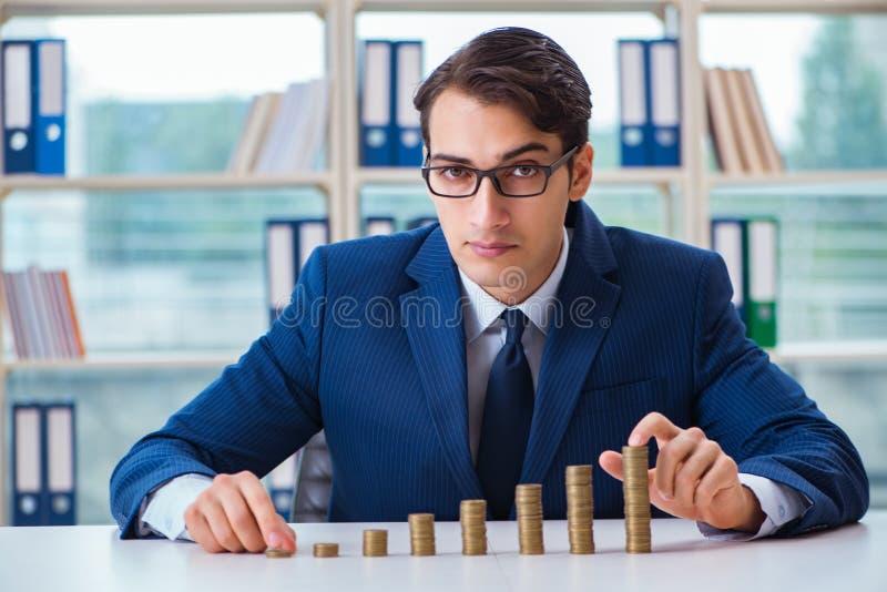 L'homme d'affaires avec des piles de pièces de monnaie dans le bureau images stock