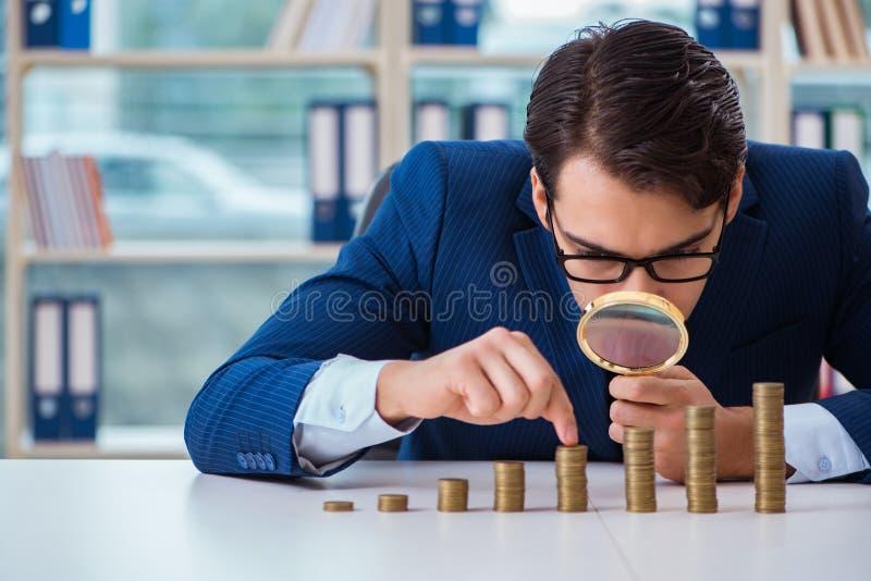 L'homme d'affaires avec des piles de pièces de monnaie dans le bureau image libre de droits