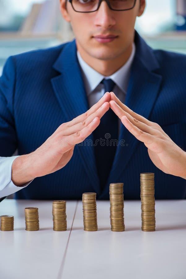 L'homme d'affaires avec des piles de pièces de monnaie dans le bureau image stock