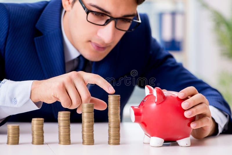 L'homme d'affaires avec des piles de pièces de monnaie dans le bureau photo libre de droits