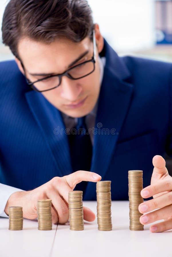L'homme d'affaires avec des piles de pièces de monnaie dans le bureau photographie stock libre de droits