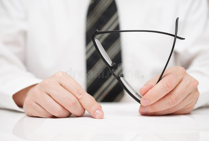 L'homme d'affaires avec des verres à disposition lit soigneusement le contrat image stock