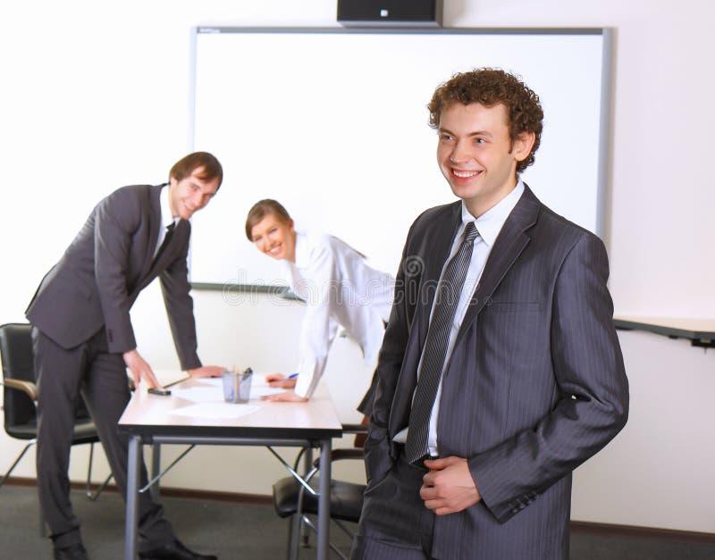 L'homme d'affaires avec l'équipe accouple à l'arrière-plan images stock