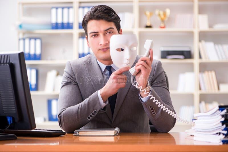 L'homme d'affaires avec le masque dans le concept d'hypocrisie de bureau image stock