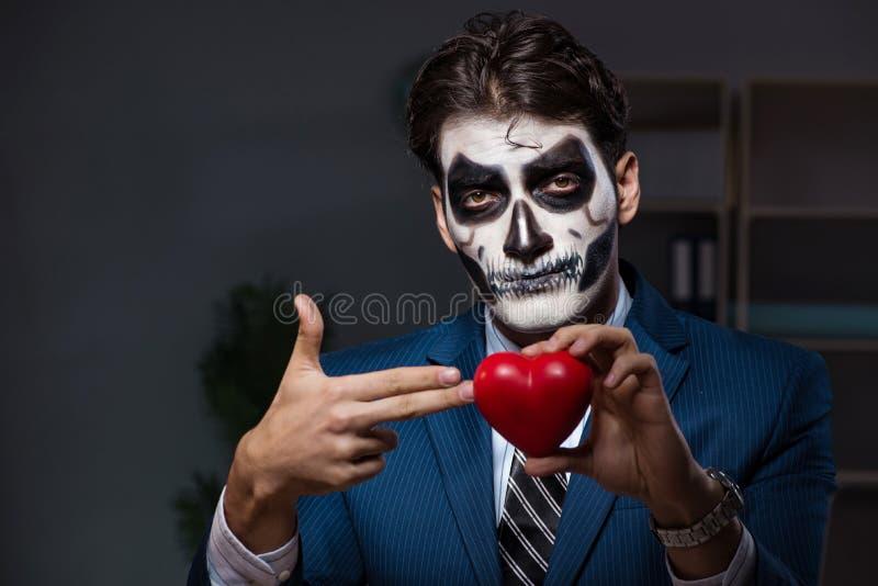 L'homme d'affaires avec le masque protecteur effrayant fonctionnant tard dans le bureau image stock
