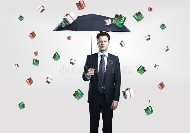 L'homme d'affaires avec le parapluie sous des cadres de cadeau pleuvoir image libre de droits