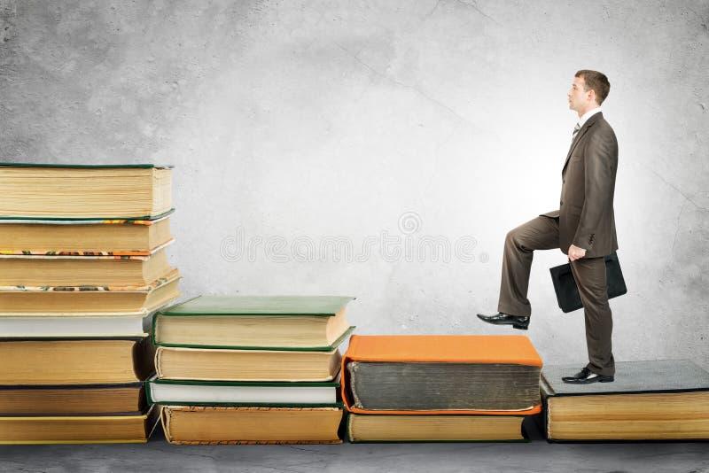 L'homme d'affaires avec le portfolio monte des escaliers des livres photos stock