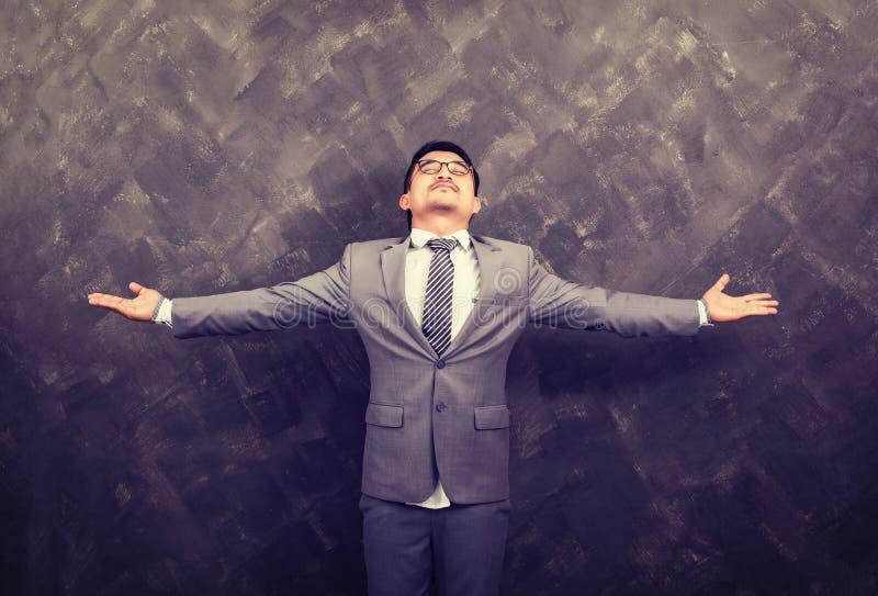 L'homme d'affaires avec le sien arme grand ouvert sur le grunch photos stock