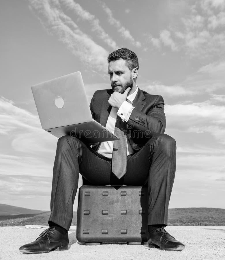 L'homme d'affaires avec l'ordinateur portable reposent le fond de ciel bleu de serviette Homme d'affaires moderne d'attribut indi photo stock