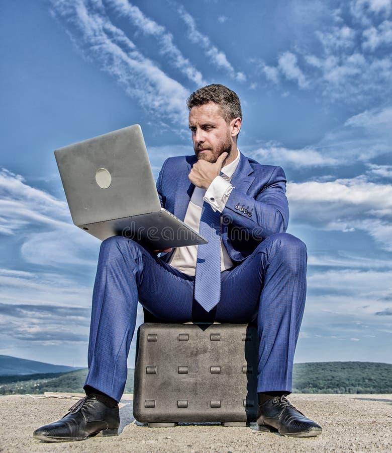 L'homme d'affaires avec l'ordinateur portable reposent le fond de ciel bleu de serviette Homme d'affaires moderne d'attribut indi images libres de droits