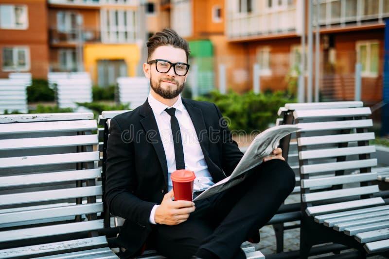 L'homme d'affaires barbu bel dans le costume classique boit du café et lit un journal tout en se reposant sur le banc dans la vil photo stock