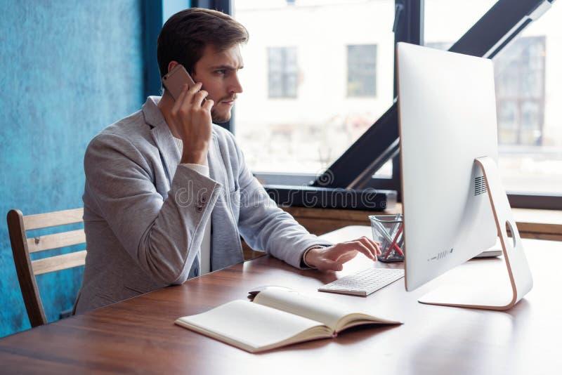 L'homme d'affaires barbu de sourire de jeunes s'assied à la table devant l'ordinateur, parlant au téléphone portable indépendant photographie stock