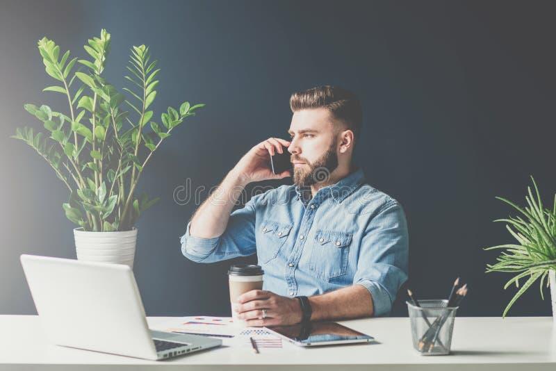 L'homme d'affaires barbu s'assied dans le bureau à la table et parle au téléphone portable tout en buvant du café image libre de droits