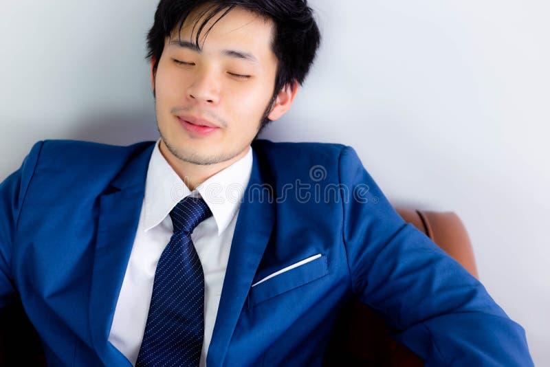 L'homme d'affaires bel de charme fait une sieste pour tandis que sur le sofa à de photos libres de droits