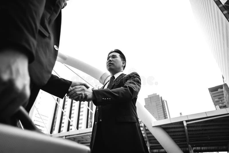 L'homme d'affaires bel est saluant et vérifiant la main à son client images stock