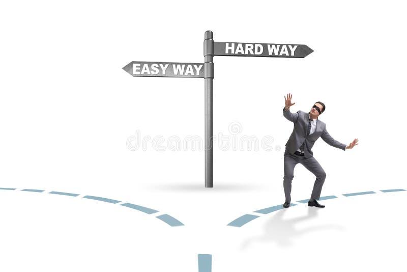 L'homme d'affaires choisissant entre les travaux forc?s et la mani?re simple image libre de droits