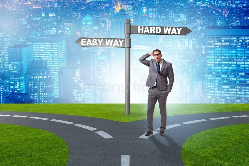 L'homme d'affaires choisissant entre les travaux forc?s et la mani?re simple image stock