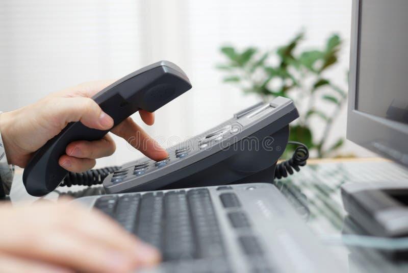 L'homme d'affaires compose un numéro de téléphone dans le bureau photo stock