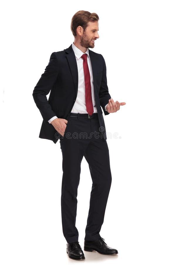 L'homme d'affaires décontracté fait le geste de invitation et regarde vers le bas au Sid photo stock