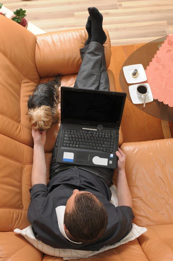 L'homme d'affaires a détendu sur le sofa avec un ordinateur portatif photos libres de droits