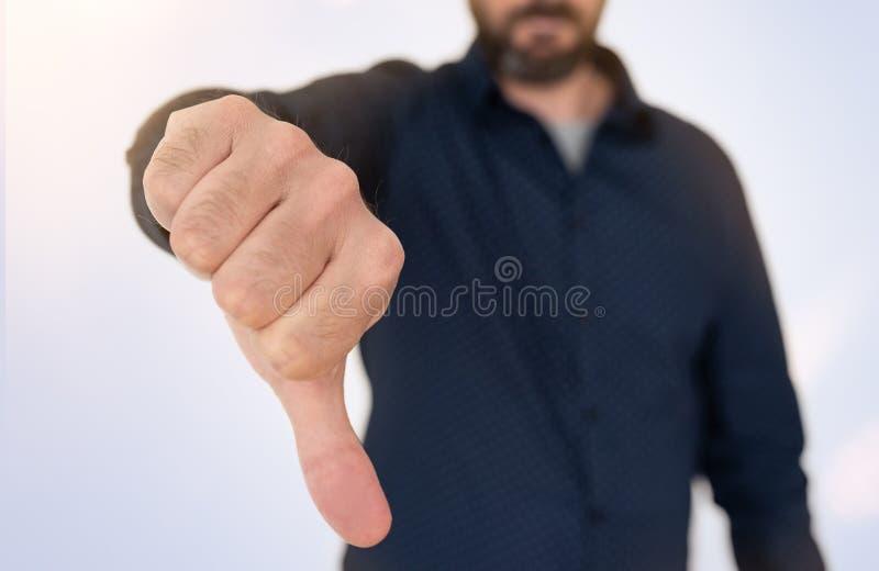 l'homme d'affaires dans la chemise bleue montrant des pouces font des gestes vers le bas photos stock