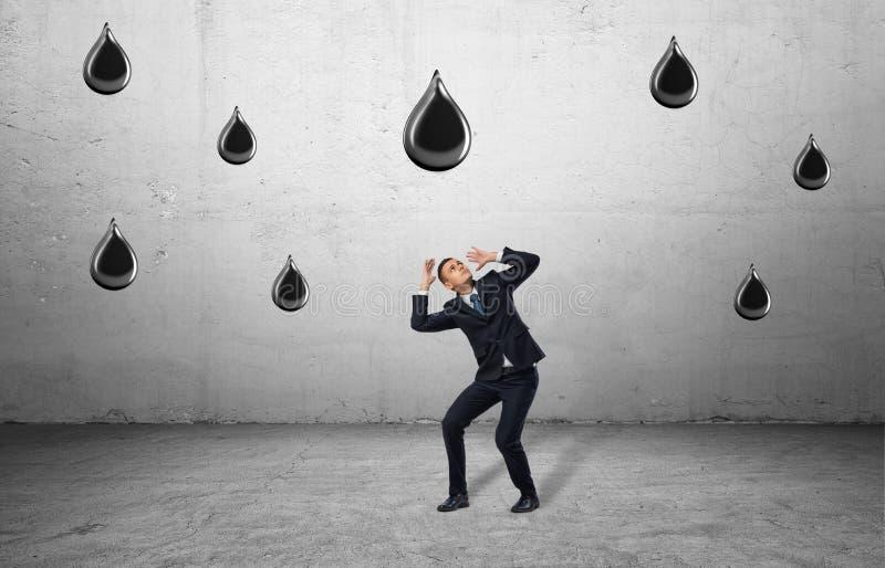 L'homme d'affaires dans la pleine croissance se protège contre des baisses en baisse énormes d'huile images libres de droits