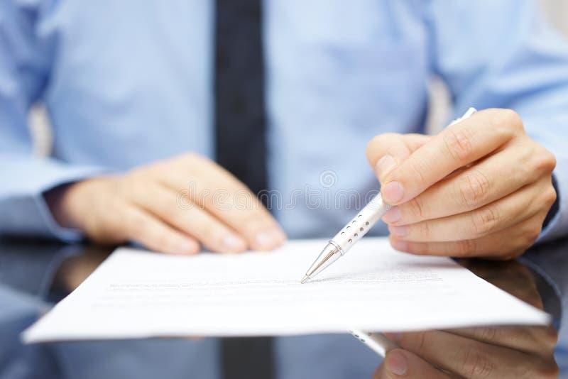 L'homme d'affaires dans le bureau analyse le document photographie stock